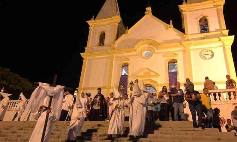 À frente, vão homens e mulheres com túnicas brancas carregando lanternas. Todos estão com o rosto coberto(foto: ESP/EM)
