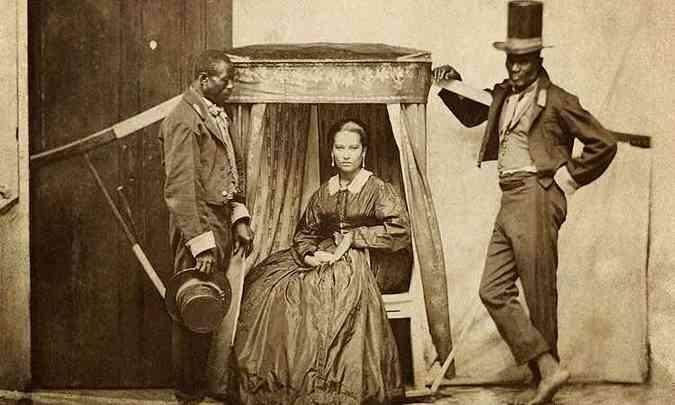 Senhora com dois escravos no Rio de Janeiro no séc. XIX - símbolo de status. Detalhe - para diferenciar os homens livres dos escravos, os últimos sempre deveriam andar descalços.(foto: Internet)